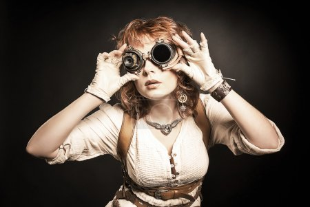 Beautiful redhair steampunk girl looking over her goggles aside
