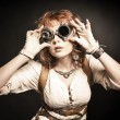 Beautiful redhair steampunk girl looking over her ...