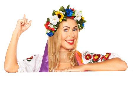 Attractive woman wears Ukrainian national dress behind board