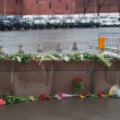 Постер, плакат: The flowers near a place of murder of the politician Boris Nemtsov and the car of police protecting the Kremlin from march of opposition