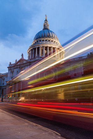 Photo for Light trails of red London buses at dawn at the St Pauls Cathedral in London, England - Royalty Free Image