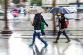 People in motion blur walking in the rainy city