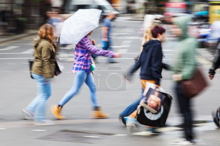 People in motion blur crossing a city street on a rainy day