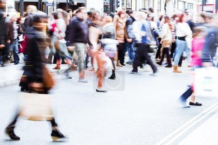 Gente en movimiento borrosa cruzando una calle en la ciudad de Londres