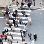 Aerial view of a crowd of people crossing a city street at a pedestrian crossing