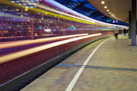 Night view of a passing train in motion blur at a train station