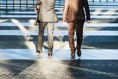 Two business people walking in an office area