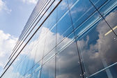 Glass facade of a modern office building with reflections in the windows