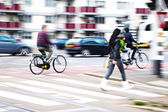 City traffic scene with cars, cycles and pedestrians