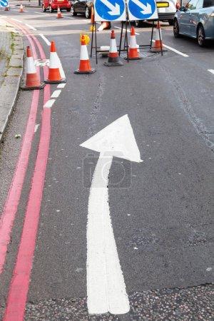 Photo pour Barrière routière à une construction routière avec une flèche de direction, des cônes de circulation et des panneaux de signalisation - image libre de droit
