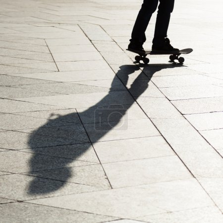 Shadow of a man with a skateboard in the city