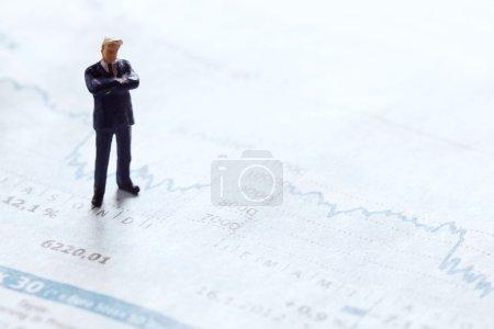 Photo pour Debout de figurine homme d'affaires sur un secteur financier d'un journal - image libre de droit