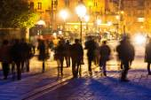 People in motion blur in the city of Paris at night