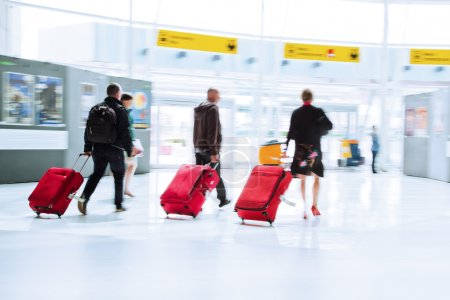 Traveling people with trolleys in motion blur at the airport