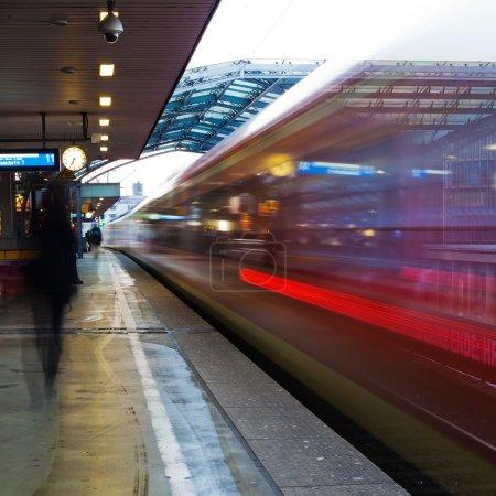 El tráfico ferroviario en movimiento se desdibuja en una plataforma de una estación ferroviaria