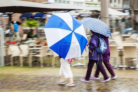 Tourists with umbrellas in a rainy European city