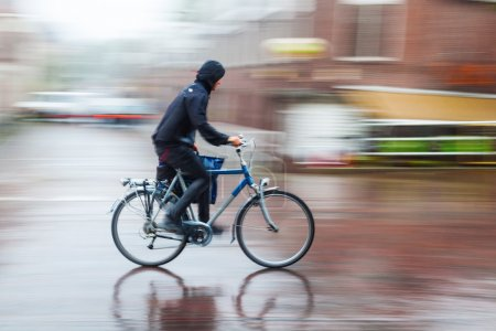 Photo for Bicycle rider on a city road in the rain - Royalty Free Image