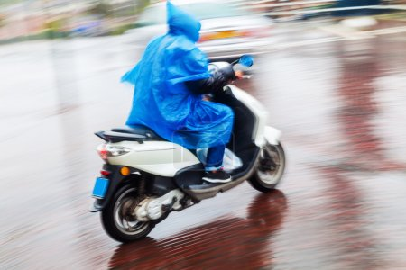 Scooterist with rain cape in motion blur