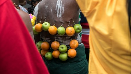 Thaipusam rituals, carry milk pots hooked on the back