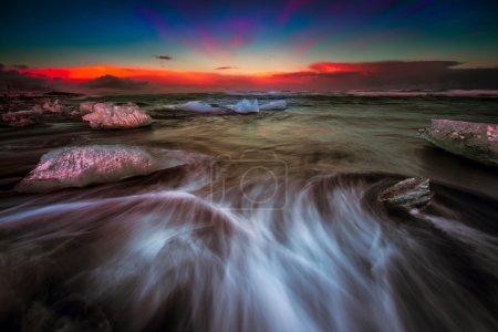 Foto de Foto de obturador lento que muestra los movimientos de las olas alrededor de los bloques de hielo que se lavan en tierra en la playa de arena negra en Islandia durante la puesta del sol. - Imagen libre de derechos