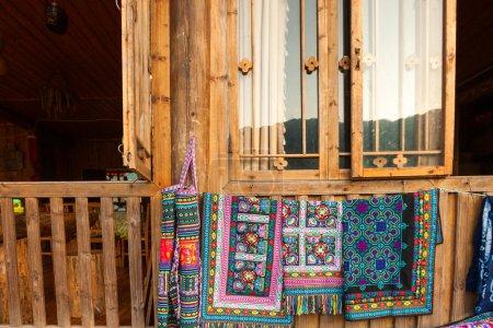 Photo pour Châle d'art tribal fabriqué par les minorités ethniques Yao de Chine accroché devant la fenêtre de la maison - image libre de droit