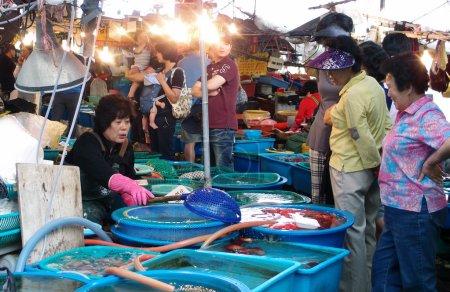 Fishmonger in Daepohang market, South Korea.