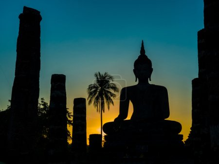 Photo for The silhouette of a statue of Buddha during sunset viewed at the Sukhothai Historical Park in Thailand. - Royalty Free Image