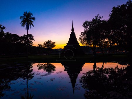 Photo for The silhouette of a pagoda with its reflection on the lake during sunset viewed at the Sukhothai Historical Park in Thailand. - Royalty Free Image