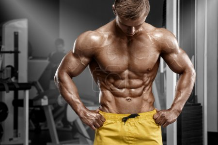 Photo for Sexy athletic man showing muscular body and sixpack abs in gym. Strong male nacked torso, working out - Royalty Free Image