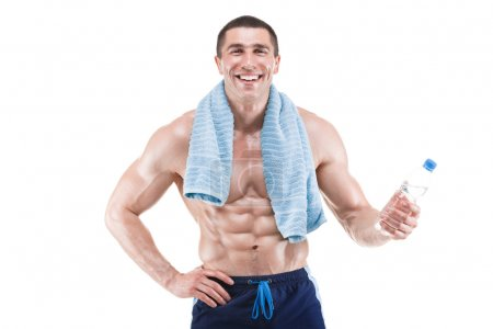 Young muscular man smiling with blue towel over neck, drinking water, isolated on white background