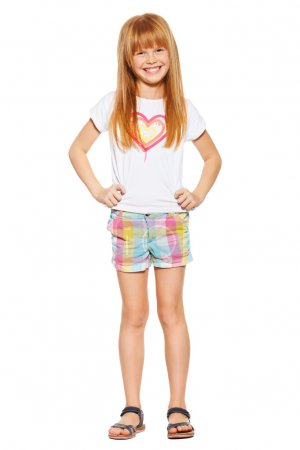 Full length a cheerful little girl with red hair in shorts and a T-shirt, isolated on the white background
