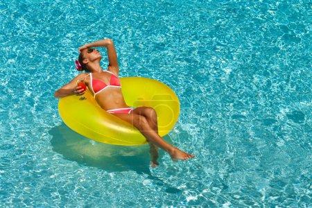 Sexy woman in bikini in pool with cocktail