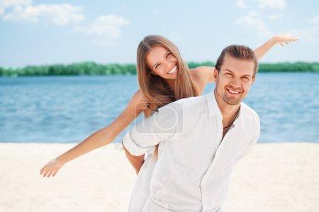Photo pour Jeunes couples joyeux heureux ayant l'amusement de plage riant ensemble pendant des vacances d'été vacances sur la plage. Beau couple frais énergique, homme et femme - image libre de droit