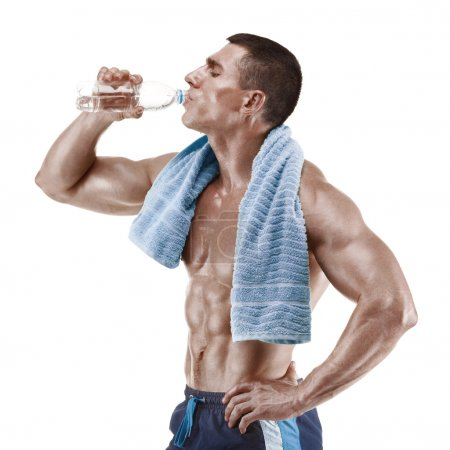 Muscular man drinking water with blue towel over neck, isolated on white background