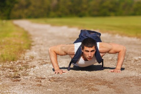 Photo for Fitness man exercising push ups, outdoor. Muscular male cross-training outside - Royalty Free Image