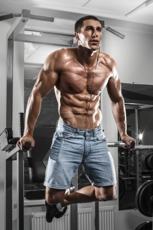 Muscular man working out in gym doing exercises on parallel bars, strong male naked torso abs
