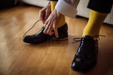 The man wears shoes. Yellow socks.