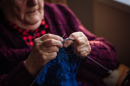The old woman sits at home and knits garments