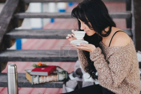Photo for Young woman having picnic: drinking tea and reading book on wooden stairs - Royalty Free Image