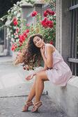 Schöne junge Frau in einem rosa Kleid posiert in einem Rosengarten