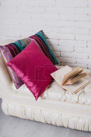 Photo pour Détails intérieurs. Mur de briques blanches. Partie de l'intérieur avec un canapé et coussins, table en bois blanc avec des livres à ce sujet - image libre de droit