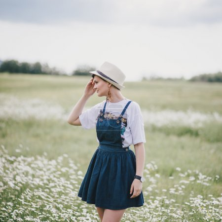 Beautiful young woman in a jeans dress and straw hat posing in a camomile field