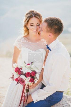 Photo pour Jeune couple heureux vient de se marier posant sur le sommet de la montagne. Jour de mariage - image libre de droit