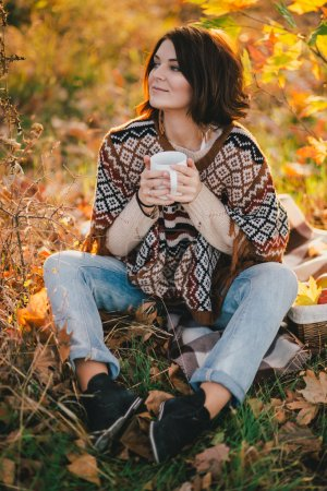 Photo for Young woman wearing knitted poncho having picnic in a forest: drinking tea and picking apples. Fall concept - Royalty Free Image