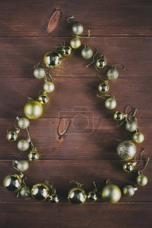 Photo for Christmas balls in a shape of Christmas tree on a wooden background. Christmas mood - Royalty Free Image