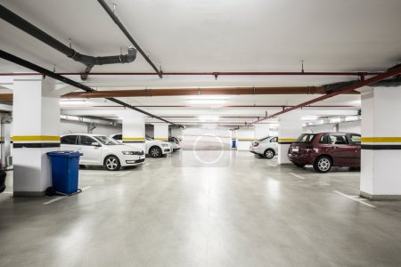 Underground parking lot, interior with a few parked cars.