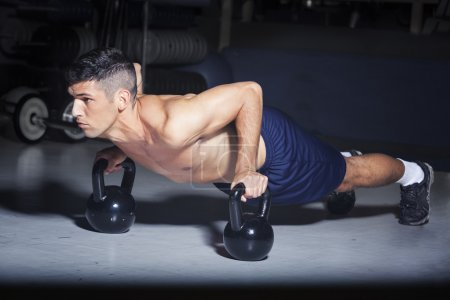 Photo for Man doing push-ups with kettlebells in gym - Royalty Free Image