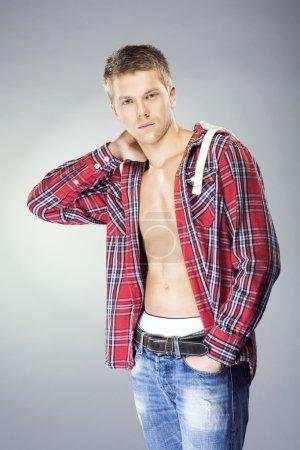 Handsome blond man in unbuttoned shirt