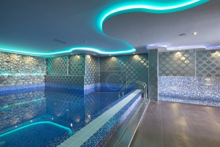 Indoors pool with colorful lights at spa center