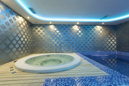 Indoors jacuzzi and pool with colorful lights at spa center